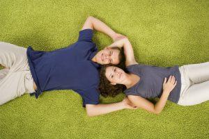 sm lying on green carpet