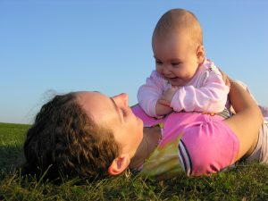baby-lying-on-mom-grass